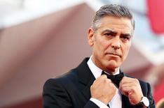 """Ator norte-americano George Clooney ajeita sua gravata ao chegar no tapete vermelho para estreia de """"Gravidade"""", durante o 70º Festival de Cinema de Veneza. Um escritório de advocacia londrino confirmou nesta segunda-feira o segredo mais público do mundo artístico, ao parabenizar nesta segunda-feira uma das suas profissionais pelo noivado com o ator George Clooney. 28/08/2013. REUTERS/Alessandro Bianchi"""