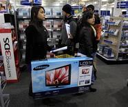 Unas personas transportan una televisión mientras realizan unas compras en una tienda de la minorista Best Buy en Framingham, EEUU, nov 25 2011. El gasto del consumidor estadounidense registró en marzo su mayor incremento en más de cuatro años y medio, afianzando las expectativas de que la economía terminó con pie firme un primer trimestre pobre. REUTERS/Adam Hunger