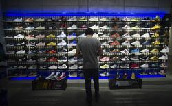 A man stands in front of a rack with Adidas Original shoes before the opening at the new Adidas Originals store in Berlin, March 27, 2014. REUTERS/Stefanie Loos