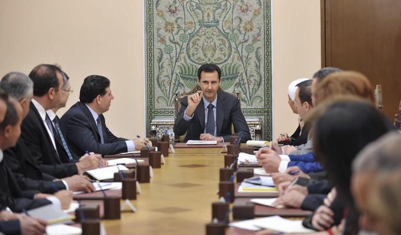 Syria's President Bashar al-Assad (C) meets with members of the Higher Committee for Relief in Damascus May 3, 2014, in this handout released by Syria's national news agency SANA. REUTERS/SANA/Handout via Reuters