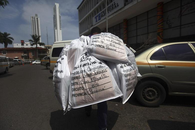 An employee of the Electoral Tribunal carries several sacks of electoral materials for distribution to various polling stations around the city, outside the Electoral Tribunal's office in Panama City May 3, 2014. Panama will hold its general elections on May 4. REUTERS/ Edgard Garrido