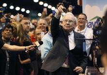 Berkshire Hathaway CEO Warren Buffett points after throwing a newspaper during a competition at a trade show, at the company's annual meeting in Omaha, Nebraska May 3, 2014. REUTERS/Rick Wilking