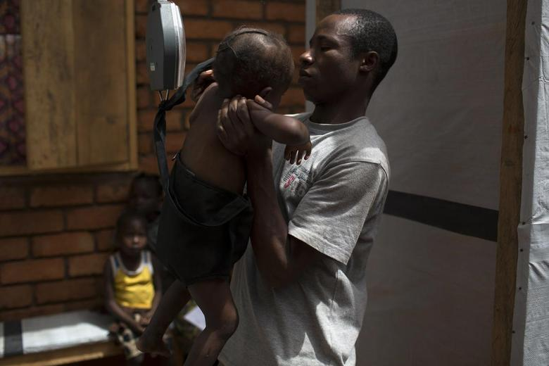 A health worker weighs a baby at a Medecins Sans Frontieres (MSF) hospital near the airport of the capital Bangui March 4, 2014. REUTERS/Siegfried Modola