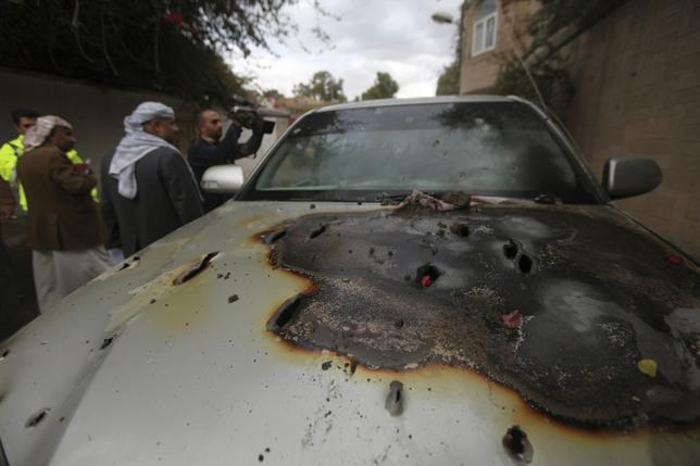 People look at a damaged car after a French man was assassinated inside, in Sanaa May 5, 2014. REUTERS/ Mohamed al-Sayaghi