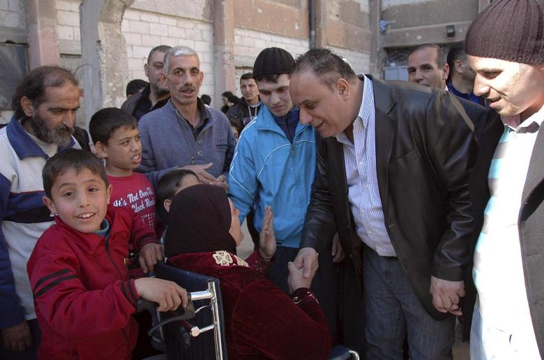 Homs Governor Talal al-Barazi (2nd R) shakes hands with a woman as he visits civilians from besieged areas of Homs living in a shelter in al-Andalus school, in an area under government control, in Homs February 14, 2014, in this handout released by Syria's national news agency SANA. REUTERS/SANA/Handout via Reuters