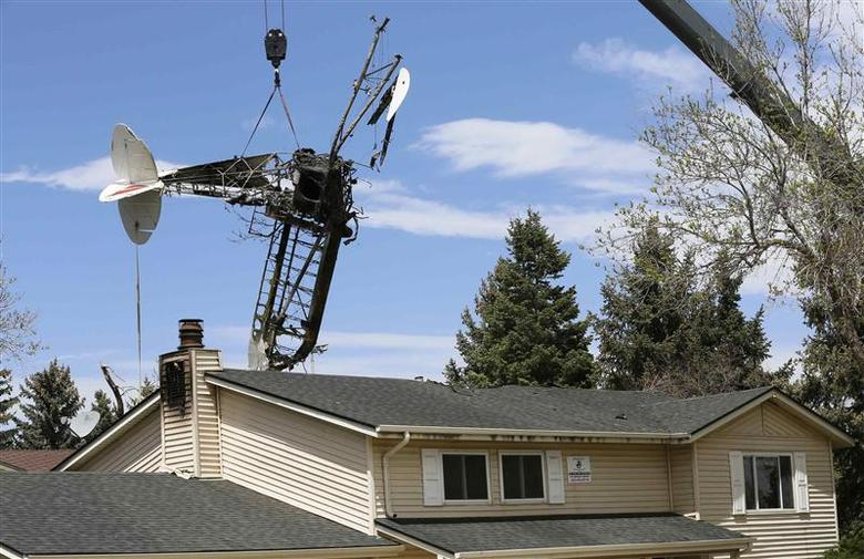 The wreckage of a small plane that crashed into a house is lifted by a crane in Northglenn, Colorado May 6, 2014. REUTERS/Rick Wilking
