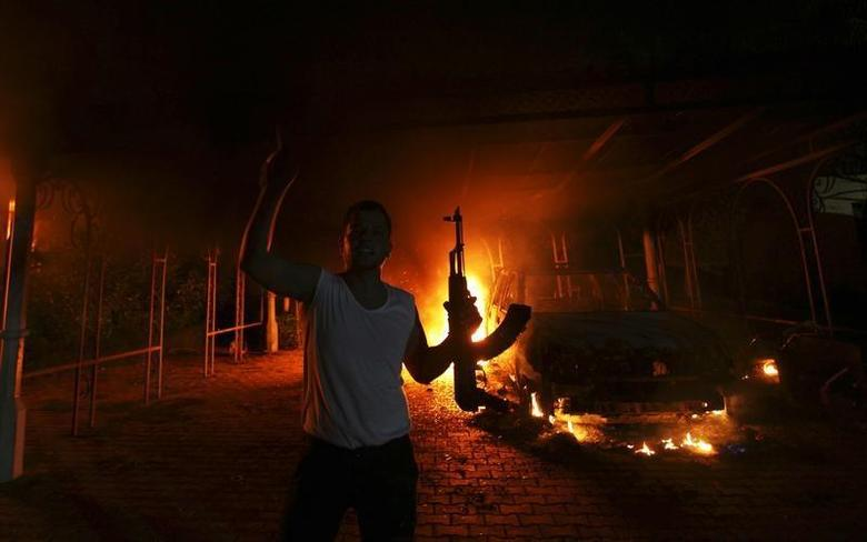 A protester reacts as the U.S. Consulate in Benghazi is seen in flames during a protest by an armed group said to have been protesting a film being produced in the United States in this file September 11, 2012 photo. REUTERS/Esam Al-Fetori