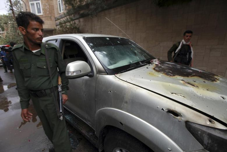 Policemen stand by a damaged car where a French man was assassinated, in Sanaa May 5, 2014. REUTERS/Mohamed al-Sayaghi