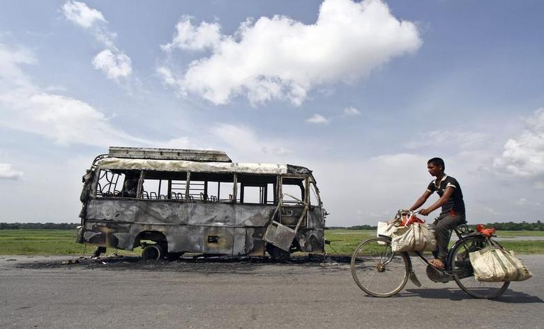 A man rides a bicycle in front of a bus that was burnt by a mob on the national highway near Rongia town in the northeastern Indian state of Assam August 16, 2012. REUTERS/Utpal Baruah