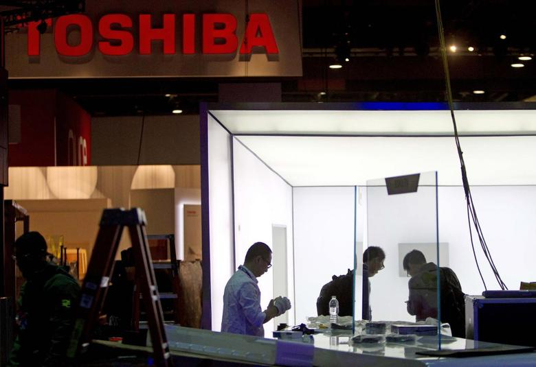 Technicians with TCL Communication put together a display near the Toshiba booth in preparation for the 2014 Consumer Electronics Show (CES) at the Las Vegas Convention Center in Las Vegas, Nevada, January 4, 2014. REUTERS/Steve Marcus