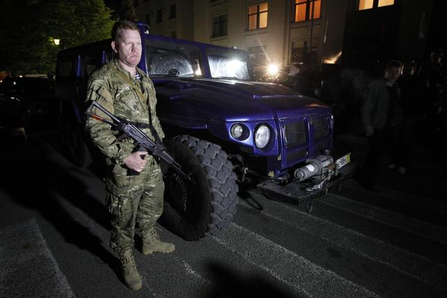 An armed pro-Russian activist stands beside a ''Tigr'' light armoured vehicle, which was a donation from the Liberal Democratic Party of Russia, in Luhansk, eastern Ukraine, May 7, 2014. REUTERS/Valentyn Ogirenko