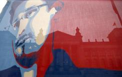 Legisladores alemanes decidieron el jueves interrogar al ex contratista de inteligencia Edward Snowden como parte de una investigación parlamentaria sobre la vigilancia masiva a ciudadanos germanos, que reveló el estadounidense. En la imagen, el edificio del Reichstag alemán a través de una bandera con un dibujo de Snowden, durante una manifestación en Berlín, el 18 de noviembre de 2013. REUTERS/Tobias Schwarz