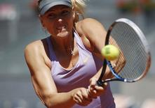 Maria Sharapova of Russia returns the ball to Li Na of China during their match at the Madrid Open tennis tournament May 9, 2014. REUTER/Andrea Comas