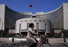 A woman rides past the headquarters of the People's Bank of China, the Chinese central bank, in Beijing, April 3, 2014. REUTERS/Petar Kujundzic