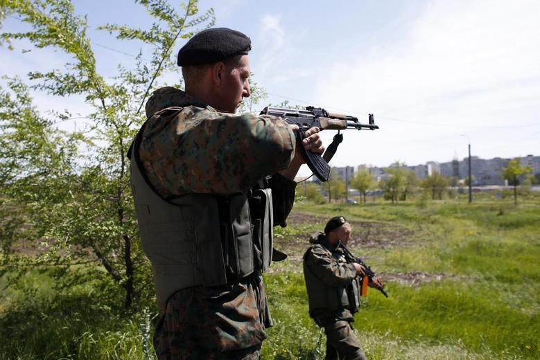 A Ukrainian soldier aims his rifle at an army checkpoint during a referendum on self-rule in the southeastern port city of Mariupol, May 11, 2014. REUTERS/Marko Djurica