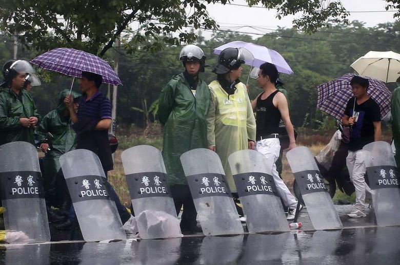 Riot police stand by the side of the road at the entrance of Yuhang town after a night of riots, west of Hangzhou, Zhejiang province May 11, 2014.  REUTERS/Carlos Barria