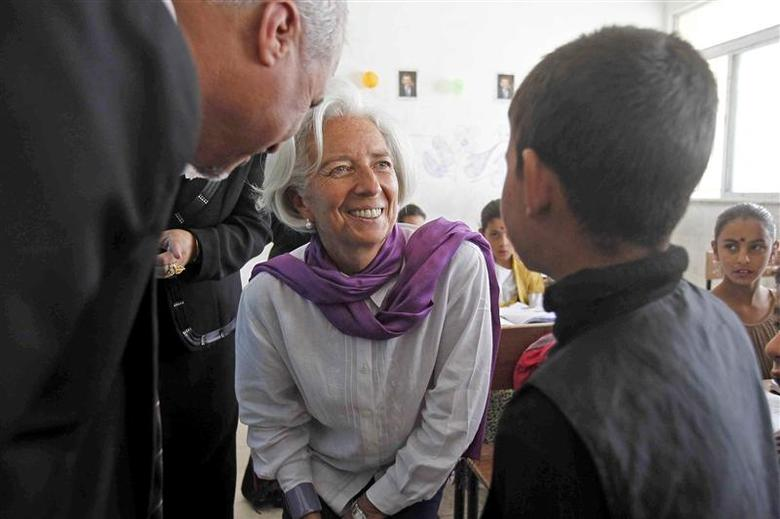 Christine Lagarde (C), International Monetary Fund Managing Director, speaks to a Syrian refugee student at Alimate school in Mafraq in this file photo from May 11, 2014. REUTERS/Ali Jarekji/Files
