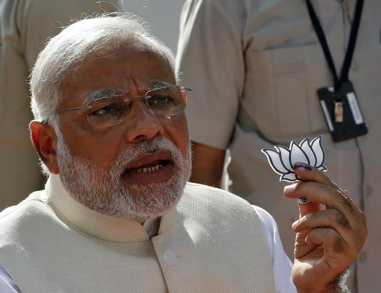 Hindu nationalist Narendra Modi, the prime ministerial candidate for India's main opposition Bharatiya Janata Party (BJP), holds a lotus cut-out after casting his vote at a polling station during the seventh phase of India's general election in the western Indian city of Ahmedabad April 30, 2014. REUTERS/Amit Dave