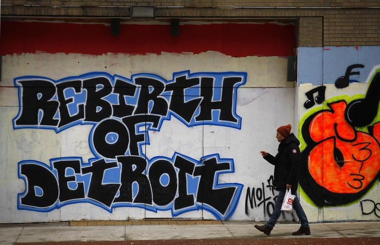 A man walks past graffiti in Detroit, Michigan, December 3, 2013. REUTERS/Joshua Lott