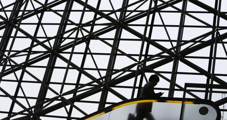 A man holding a mobile phone rides an escalator in Tokyo August 11, 2013. REUTERS/Yuya Shino