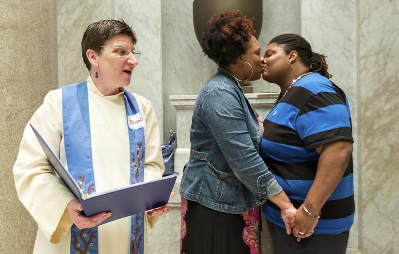 Rev. Jennie Barrington (L) performs the marriage ceremony of Amanda Boyd and Narkisha Scott (R) at the Pulaski County Courthouse in Little Rock, Arkansas May 12, 2014. REUTERS/Jacob Slaton