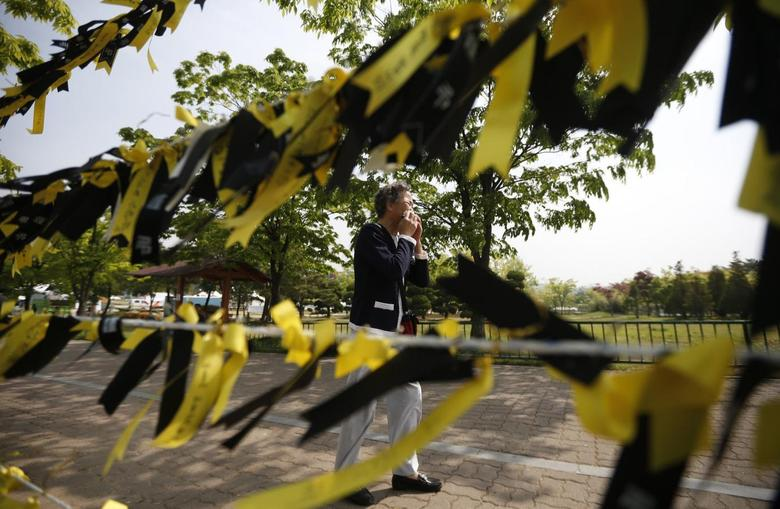 A mourner cries next to yellow ribbons dedicated to missing and dead passengers of sunken passenger ship Sewol, after paying tribute at the official memorial altar in Ansan May 2, 2014. REUTERS/Kim Hong-Ji