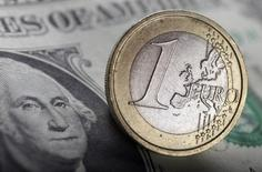 Монета 1 евро на долларовой банкноте, Варшава, 26 января 2011 года. Курс евро к доллару поднялся с минимума 2,5 месяцев за счет фиксации прибыли перед выходными. REUTERS/Kacper Pempel