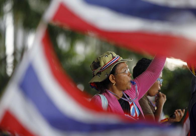 An anti-government protester blows her whistle during a rally outside the office of Election Commission in Bangkok May 15, 2014. REUTERS/Chaiwat Subprasom
