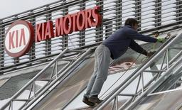 A worker repairs a roof next to a Kia Motors logo in Prague October 9, 2012. REUTERS/David W Cerny
