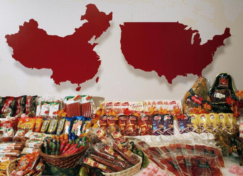 Some of the products of WH Group are displayed in front of maps of China (L) and the United States at a news conference on the company's IPO in Hong Kong, in this April 14, 2014 file photo. REUTERS/Bobby Yip/Files