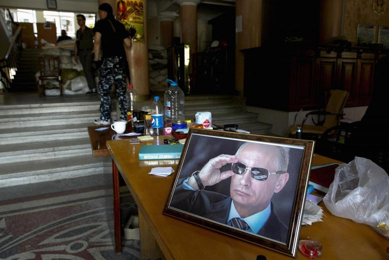 A portrait of Russian President Vladimir Putin is displayed on a table in the hall of a regional administration building occupied by pro-Russian activists in the eastern Ukrainian city of Luhansk May 17, 2014. REUTERS/Valentyn Ogirenko