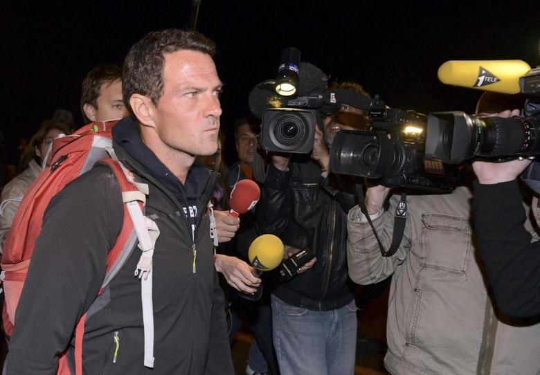 Journalists surround convicted rogue trader Jerome Kerviel (L) as he arrives on the Franco-Italian border in Menton, May 18, 2014. REUTERS/Jean-Pierre Amet