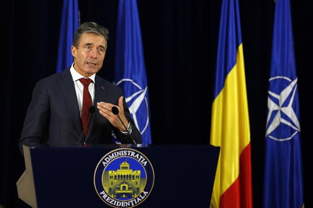 NATO Secretary-General Anders Fogh Rasmussen gestures during a joint news conference with Romania's President Traian Basescu (not in picture) at Cotroceni Presidential Palace in Bucharest May 16, 2014. REUTERS/Bogdan Cristel