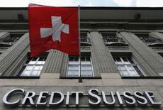 The logo of Swiss bank Credit Suisse is seen below the Swiss flag at a building in the Federal Square in Bern May 15, 2014. REUTERS/Ruben Sprich