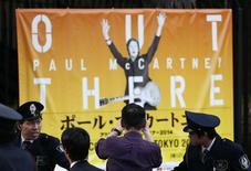 """Un aficionado toma una fotografía a un afiche de un concierto de Paul McCartney tras su cancelación en Tokio, mayo 18 2014. El ex Beatle Paul McCartney ha cancelado su gira """"Out There"""" en Japón por un empeoramiento de una infección viral que le exige reposo total, dijeron el martes los organizadores del concierto.        REUTERS/Toru Hanai"""