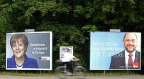 A cyclist passes European election posters of Socialist candidate for European Commission president Martin Schulz (R) of the Social Democratic Party (SPD) and German Chancellor and head of the Christian Democratic Union (CDU) Angela Merkel, in Hamburg, May 20, 2014.  REUTERS/Fabian Bimmer