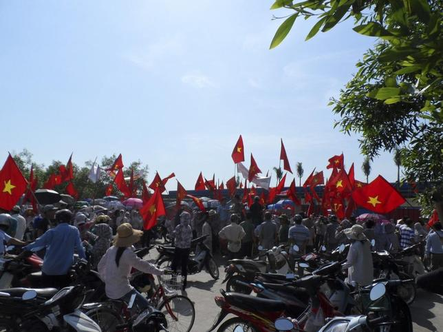 Workers wave Vietnamese national flags during an anti-China protest at a Chinese-owned shoe factory in Vietnam's northern Thai Binh province May 14, 2014. REUTERS/Stringer