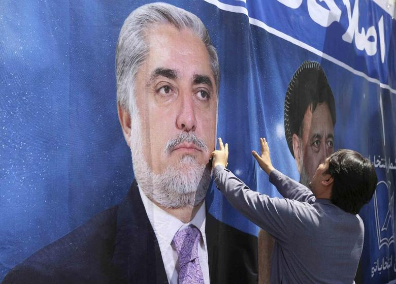 A man installs a banner of presidential candidate Abdullah Abdullah during the first day of the second round presidential election campaign in Kabul May 22, 2014. REUTERS/Omar Sobhani