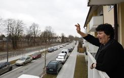 Иммигрант из Греции Мария Затсе машет друзьям с балкона своей однокомнатной квартиры в Мюнхене 19 марта 2012 года. Чистая миграция в Германию выросла до максимума 20 лет в 2013 году, при этом большинство иммигрантов прибыли из пострадавших от кризиса Италии и Испании, а также Польши, свидетельствуют данные Статистического бюро. REUTERS/Michaela Rehle