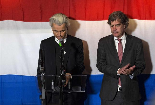 Far-right politician Geert Wilders of the anti-immigration Dutch Freedom (PVV) Party (L) and PVV candidate Marcel De Graaff react at a PVV rally after the European Parliament elections in the Hague May 22, 2014. REUTERS/Michael Kooren