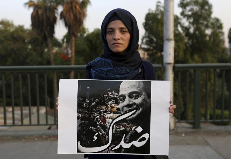 A woman carries a poster of presidential candidate and former army chief Abdel Fattah al-Sisi, with the slogan ''Against you'', during a protest on the 6th October bridge near Tahrir square in Cairo May 22, 2014. REUTERS/Mohamed Abd El Ghany