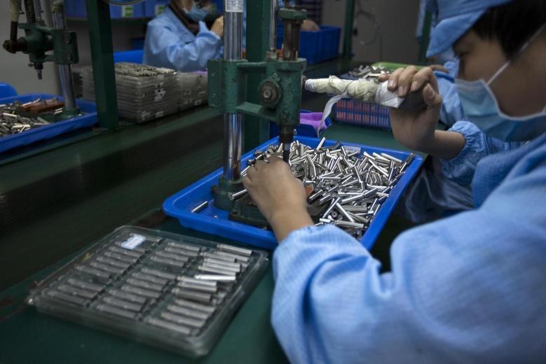 Employees work on electronic cigarettes at a production line in a factory in Shenzhen, southern Chinese province of Guangdong January 15, 2014. REUTERS/Tyrone Siu