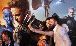 Cast members Hugh Jackman and Fan Bingbing take photos as Peter Dinklage (L) waves to fans at the South East Asia premiere of X-Men: Days Of Future Past in Singapore May 14, 2014.  REUTERS/Edgar Su