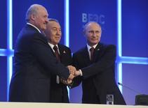 Le président russe, Vladimir Poutine (à droite), aux côtés du président kazakh, Nursultan Nazarbaïev (au centre), et de leur homologue biélorusse, Alexander Loukachenko, après la signature d'un traité portant la création d'une Union économique eurasienne entre les trois pays, un bloc commercial censé concurrencer les Etats-Unis, l'Union européenne et la Chine. /Photo prise le 29 mai 2014/REUTERS/Mikhail Klimentyev/RIA Novosti/Kremlin