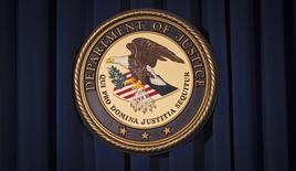 The Department of Justice (DOJ) logo is pictured on a wall after a news conference in New York December 5, 2013.     REUTERS/Carlo Allegri