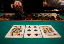A dealer picks up chips on a mock black jack casino table during a photo opportunity at an international tourism promotion symposium in Tokyo September 28, 2013. REUTERS/Yuya Shino