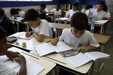 "Children read state-issued textbooks from the ""Bicentennial Collection""  at a classroom of the Eleazar Lopez Contreras school in Caracas May 23, 2014. Venezuela's government has published dozens of new textbooks that glorify late president Hugo Chavez and belittle his adversaries, infuriating opposition critics who call them part of a campaign to indoctrinate school children. REUTERS/Carlos Garcia Rawlins"