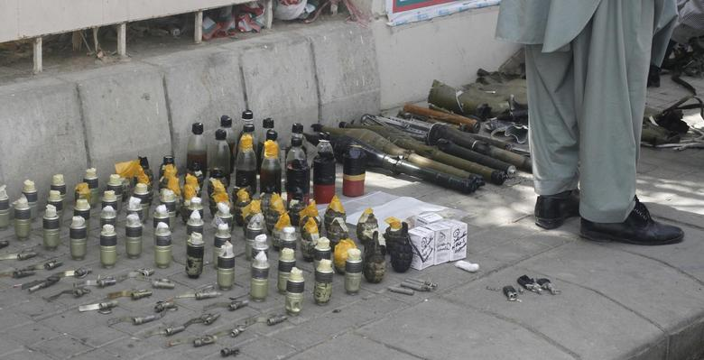 A member of the Bomb Disposal Squad (BDS) stands near to the explosives and hand grenades, which have been defused, along a sidewalk outside Jinnah International Airport Karachi June 9, 2014. REUTERS/Athar Hussain