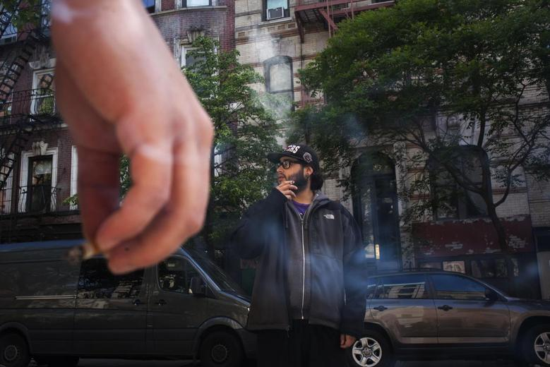 Twenty-one year old men smoke outside a friend's apartment in Lower Manhattan, New York May 18, 2014.  REUTERS/Eric Thayer