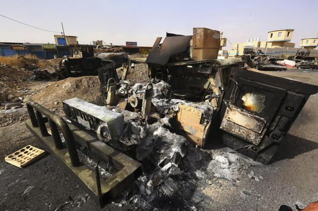 Burnt vehicles belonging to Iraqi security forces are pictured at a checkpoint in east Mosul, one day after radical Sunni Muslim insurgents seized control of the city, June 11, 2014.  REUTERS/Stringer